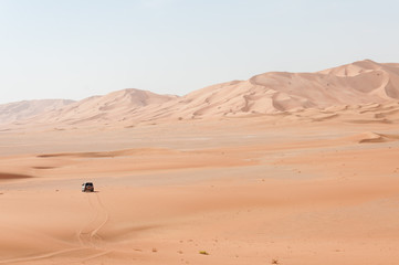 Car among sand dunes in Oman desert (Oman)