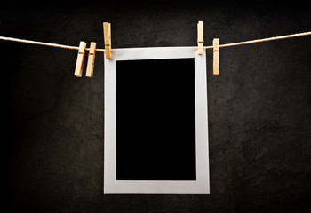 Photography paper attached to rope with clothes pins.