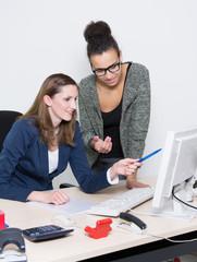Zwei Frauen diskutieren vor dem Computer im Büro
