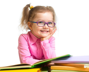 Happy smiling kid girl in glasses reading books sitting at table