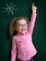 Happy kid girl in glasses with bright idea standing near school