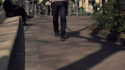 Man walking on pavement in the city, super slow motion