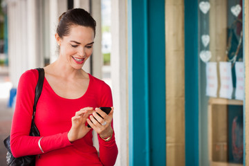 Smiling woman texting on mobile phone