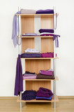 Tidy wardrobe with purple clothes nicely arranged on a shelf. poster