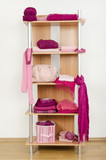 Tidy wardrobe with pink clothes nicely arranged on a shelf. poster