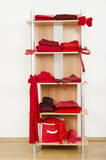 Tidy wardrobe with red clothes nicely arranged on a shelf. poster