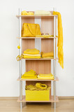 Tidy wardrobe with yellow clothes nicely arranged on a shelf. poster