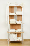 Tidy wardrobe with white clothes nicely arranged on a shelf. poster