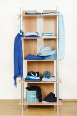 Tidy wardrobe with blue clothes nicely arranged on a shelf.