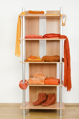 Tidy wardrobe with orange clothes nicely arranged on a shelf.