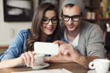 Fototapety Hipster couple using mobile phone at cafe