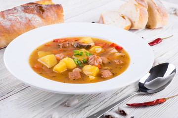 .Hungarian goulash with beans and peppers on wooden board