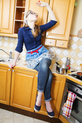 Woman on kitchen furniture eat long noodle