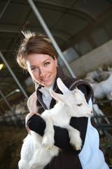 Cheerful farmer woman carrying baby goat in barn