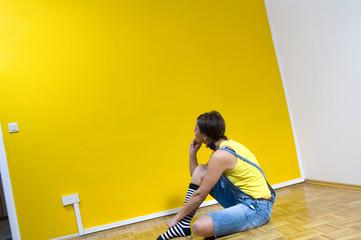 Frau sitzt auf Boden , Blick auf gelbe Wand