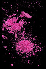Pink makeup powder explosion suspension on black background