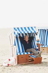 Deutschland,St. Peter-Ording,Nordsee,älterer Mann entspannt auf Strandkorb