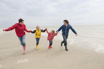 Deutschland,St. Peter-Ording,Nordsee,Familie Hand in Hand und läuft am Strand