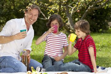 Vater und Kinder (8-11) mit Getränk beim Picknick