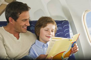 Deutschland,München,Bayern,Mann und Junge Lesebuch in der Economy Class -Verkehrsflugzeug