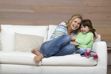 Mutter und Tochter ( 6-7) sitzen auf Sofa,lächelnd,Porträt