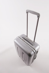 Silber Koffer mit langem Griff vor weißem Hintergrund