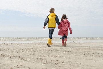 Deutschland,St. Peter-Ording,Nordsee,Junge und Mädchen (6-9) den Händen halten und zu Fuß am Strand