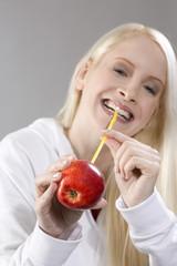 Junge Frau hält einen Apfel mit einem Strohhalm, lächelnd, Porträt