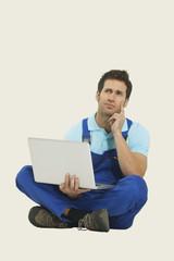 Mann im Gesamt sitzt mit Laptop