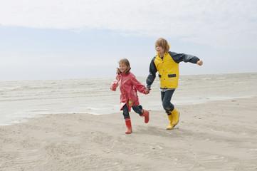 Deutschland,St. Peter-Ording,Nordsee,Junge und Mädchen (6-9) Hand in Hand und läuft am Strand