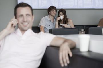 Deutschland,Köln,Paar im Café,Mann im Vordergrund mit Handy