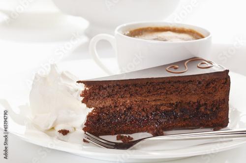 Scheibe der Sachertorte in der Platte mit Kaffeetasse im Hintergrund