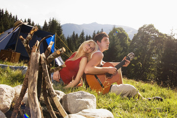 Junges Paar in der Wiese sitzt,Mann spielt Gitarre