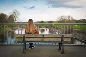 frau sitzt einsam auf einer parkbank
