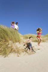 Deutschland,Ostsee,Familie in Sanddünen,Kinder springen hinunter Sanddünen