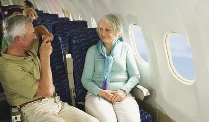 Deutschland,München,Bayern,älterer Mann,der Foto aus Handy in der Economy-Klasse -Verkehrsflugzeug