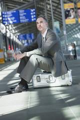 Deutschland,Leipzig -Halle,Flughafen,Geschäftsmann sitzt auf Koffer