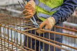 workers hands using steel wire and pincers to secure rebar 2 poster