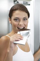 Junge Frau isst Schokolade
