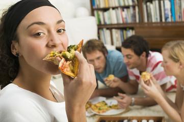 Vier junge Leute liegen auf dem Boden,essen Pizza
