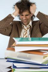 Man sitzt am Schreibtisch mit aufgetürmt Dateien