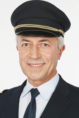 Flugkapitän vor weißem Hintergrund,lächelnd,Porträt