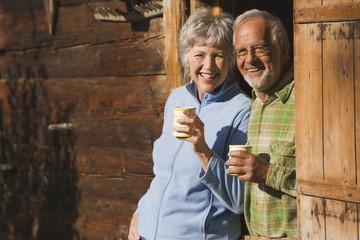 Österreich,Karwendel,älteres Paar stützte sich auf Blockhütte,halten Becher,lächelnd,Porträt