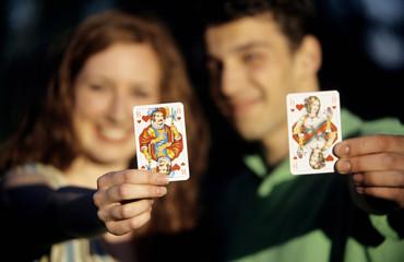 Junge Paare,die Spielkarten,Fokus auf den Karten im Vordergrund,close-up