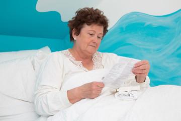 Portrait einer alten kranken Frau im Bett - Pflege von Senioren
