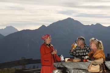Bäuerin serviert Paar an Hütten