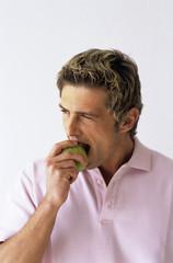 Junger Mann beißt Apfel,close-up