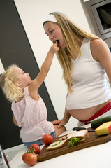 Tochter ( 3-4 ) Fütterung schwangere Mutter Gurkenscheibe