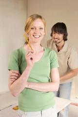 Junge Paare,die Renovierung,Frau im Vordergrund Haltestift,lächelnd,Porträt