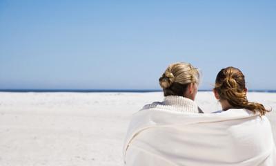 Mutter und Tochter sitzen am Strand